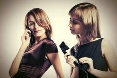 Deux jeunes femmes de mode avec le téléphone mobile et rétro Images stock