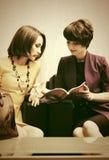 Deux jeunes femmes de mode lisant un magazine dans la salle d'exposition Images stock
