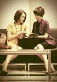 Deux jeunes femmes de mode s'asseyant sur le divan dans la salle d'exposition Photos libres de droits