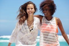 Deux jeunes femmes de sourire appréciant la plage Image libre de droits