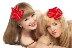 Deux jeunes femmes de sourire avec la proue rouge de cadeau Photographie stock libre de droits