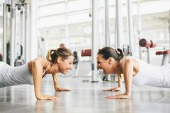 Deux jeunes femmes de sourire s'exerçant dans un gymnase Images libres de droits