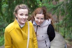 Deux jeunes femmes de sourire se tenant ensemble et regardant l'appareil-photo Photos stock