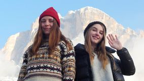 Deux jeunes femmes de sourire tenant sur un fond de des montagnes et ondulant avec leur main banque de vidéos