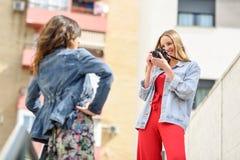 Deux jeunes femmes de touristes prenant des photographies dehors Image stock