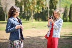 Deux jeunes femmes de touristes prenant des photographies dehors Photographie stock