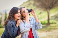 Deux jeunes femmes de touristes prenant des photographies dehors Photo libre de droits