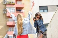 Deux jeunes femmes de touristes prenant des photographies dehors Photo stock