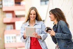 Deux jeunes femmes de touristes regardant des cartes avec le comprimé numérique extérieur Photographie stock