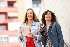 Deux jeunes femmes de touristes regardant des cartes avec le comprimé numérique extérieur Images libres de droits