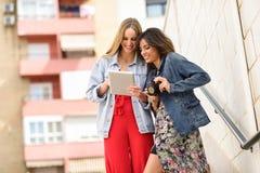 Deux jeunes femmes de touristes regardant des cartes avec le comprimé numérique extérieur Photos libres de droits