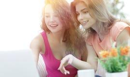 Deux jeunes femmes discutent la vidéo avec l'ordinateur portable se reposant à un coffe Photographie stock libre de droits