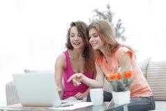 Deux jeunes femmes discutent la vidéo avec l'ordinateur portable se reposant à une table basse Photographie stock libre de droits