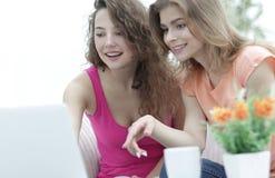 Deux jeunes femmes discutent la vidéo avec l'ordinateur portable se reposant à une table basse Photo stock