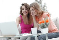 Deux jeunes femmes discutent la vidéo avec l'ordinateur portable se reposant à une table basse Images libres de droits