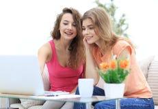 Deux jeunes femmes discutent la vidéo avec l'ordinateur portable se reposant à une table basse Image stock