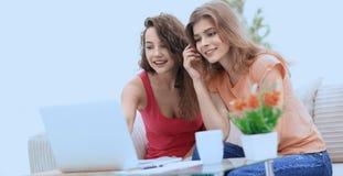Deux jeunes femmes discutent la vidéo avec l'ordinateur portable se reposant à une table basse Photos stock