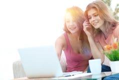 Deux jeunes femmes discutent la vidéo avec l'ordinateur portable se reposant à une table basse Images stock
