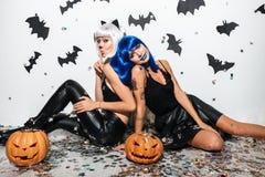 Deux jeunes femmes drôles dans la pose en cuir de costumes de Halloween Photo libre de droits