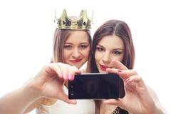 Deux jeunes femmes drôles prenant le selfie Images stock