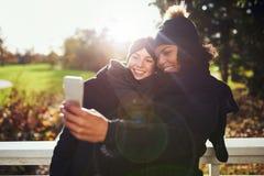 Deux jeunes femmes en parc prenant le selfie Images stock