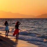 Deux jeunes femmes en silhouette sur un coucher du soleil échouent on posant pour une photo contre un beau ciel orange de soirée  Photographie stock libre de droits