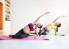 Deux jeunes femmes enceintes faisant des exercices de forme physique Photographie stock libre de droits