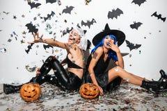 Deux jeunes femmes enthousiastes dans des costumes en cuir de Halloween Photos stock