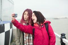 Deux jeunes femmes espiègles posant pour un selfie Images stock