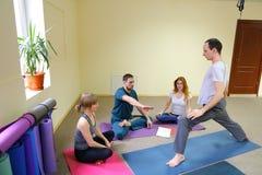 Deux jeunes femmes et deux hommes s'asseyent sur le plancher dans le studio de forme physique Photos stock