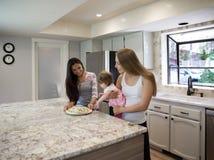Deux jeunes femmes et petite fille dans la cuisine Photo stock