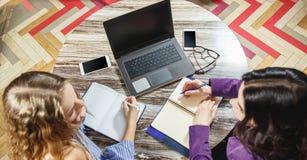 Deux jeunes femmes faisant des disques dans un carnet dans une vue supérieure de bureau Ordinateur portable, verres, téléphone in images stock