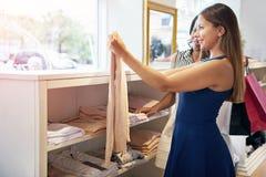 Deux jeunes femmes faisant des emplettes dans un magasin d'habillement Photo stock