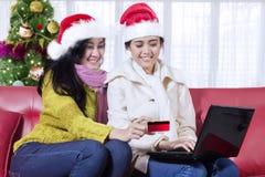Deux jeunes femmes faisant des emplettes en ligne avec l'ordinateur portable Image libre de droits