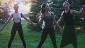 Deux jeunes femmes faisant des exercices de yoga avec l'entraîneur en parc à la lumière du soleil - une femme a de longs dreadloc clips vidéos