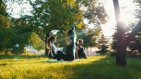 Deux jeunes femmes faisant des exercices de yoga avec l'entraîneur en parc dans les rayons du soleil - une femme a de longs dread banque de vidéos