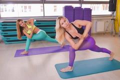 Deux jeunes femmes faisant l'asana de yoga, la forme physique et le concept de mode de vie Images stock