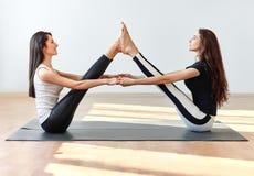 Deux jeunes femmes faisant la pose de bateau d'ami d'asana de yoga Images stock