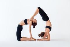 Deux jeunes femmes faisant la pose et le scorpion de chameau d'asana de yoga d'associé Photos libres de droits