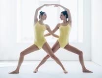 Deux jeunes femmes faisant la variation de pose de guerrier d'asana de yoga Photographie stock libre de droits