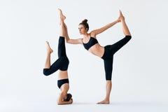 Deux jeunes femmes faisant le seigneur d'asana de yoga d'associé de la danse et du H Image libre de droits