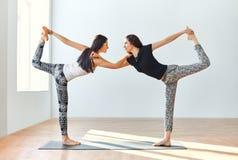 Deux jeunes femmes faisant le seigneur d'asana de yoga de la danse posent Image libre de droits