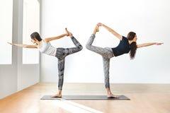 Deux jeunes femmes faisant le seigneur d'asana de yoga de la danse posent Photos libres de droits