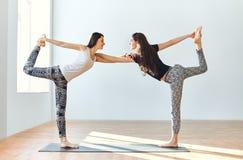 Deux jeunes femmes faisant le seigneur d'asana de yoga de la danse posent Photo libre de droits