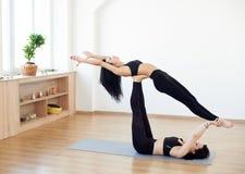 Deux jeunes femmes faisant le yoga avanc? pratiquant la pose volante ?lev?e de yoga d'acro de baleine Activit?s modernes et mode  photos libres de droits