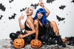 Deux jeunes femmes gaies dans des costumes en cuir de Halloween Photo stock