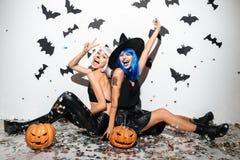 Deux jeunes femmes gaies dans des costumes en cuir de Halloween Photographie stock libre de droits