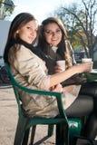 Deux jeunes femmes heureuses buvant du café et du thé Photographie stock libre de droits