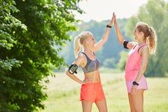 Deux jeunes femmes heureuses de courir ensemble Image stock