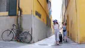 Deux jeunes femmes heureuses de déplacement marchant avec un bagage autour des murs jaunes clips vidéos